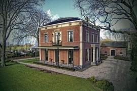 """<strong>Rietveld, Villa Kop en Hagen</strong><br>Het landhuis """"Kop en Hagen"""" kent een rijke historie en is een Rijkmonument. Op deze plaats stond al in 1678 een steenoven. In 1737 werd er op deze plaats een steenfabriek neergezet en op dat moment wordt de fabriek en de oven de naam """"Kop en Hagen"""" meegegeven. Diverse generaties Knijff zijn eigenaar geweest van de steenfabriek. De familie Knijff had in die tijd meer steenfabrieken en pannenbakkerijen. Tot 1938 zal de steenfabriek open blijven. Als de steenfabriek eenmaal gesloten is blijft alleen het landhuis over. Het neoclassicistisch landhuis """"Kop en Hagen"""", type herenhuis met bijbehorend koetshuis is in 1857-1858 gebouwd voor Aart Knijff Hz., steenfabrikant te Woerden en van 1877 tot 1907 burgemeester van Barwoutswaarder, Waarder en Rietveld. <br>De omringende tuin wordt aan de straatzijde afgesloten door een smeedijzeren spijlenhekwerk met twee toegangshekken tussen betonnen hekpijlers. Het toegangshek is afkomstig van de gesloopte villa Koole (Westdam) in Woerden In de tuin met een gazon staan diverse heesters en solitairbomen, waaronder een monumentale plataan. Aan de overzijde van de weg ligt aan de rivier de Oude Rijn een smalle overtuin met een klein prieel en twee oude magnolia bomen alsmede de koetsierswoning met paardenstal. Wil je meer foto's zien van villa Kop en Hagen, kijk dan in het menu links."""